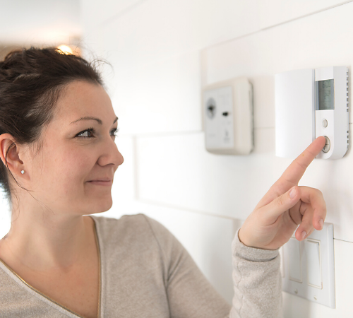 woman pressing button on heating thermostat