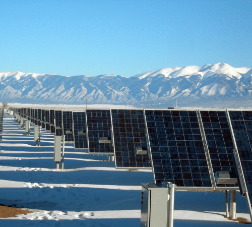 Solar panels in snow by mountains