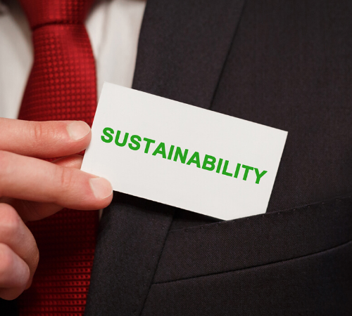 Man in suit putting card with word 'sustainability' in pocket