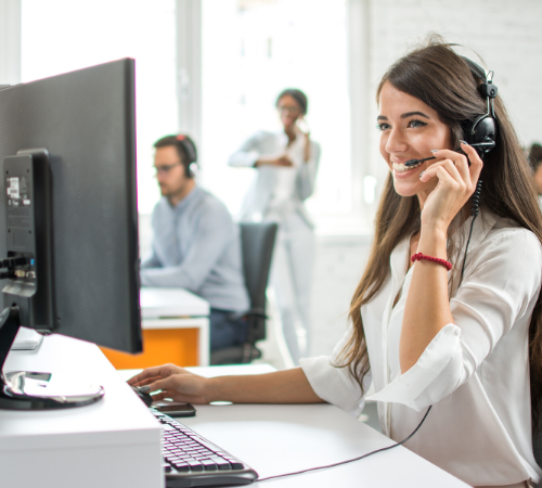 woman on customer service team smiling with headset on