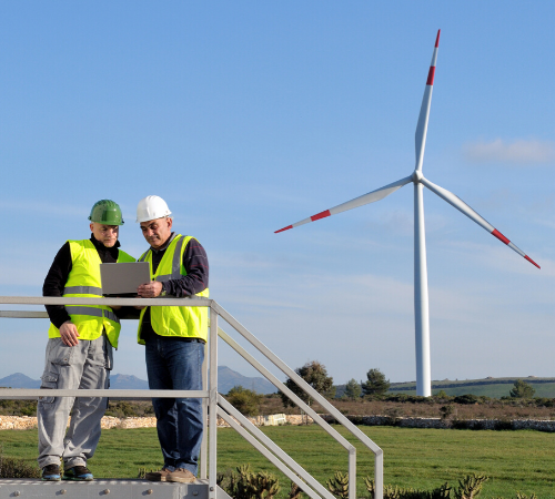 workers looking at laptop by wind turbine